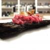 Bistecca primitiva: su una corteccia di pino marittino della carne della Garfagnana battuta grossolanamente è accompagnata da chips di buccia di patata. Classico di Tomei, la corteccia bruciacchiata fa sì che il piatto simuli gli aromi e la succulenza della carne grigliata