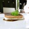 Branzino, riccio di cipollotto, fumetto di pesce allo zenzero con semi di soia fermentati, per un retogusto amarognolo. Il pesce viene cotto al vapore di vino di riso, la pelle in salamandra per renderla croccante