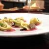 Tortelli di pesto su carpaccio di manzo affumicato, lumache di vigna, pinoli, salsa di zenzero e olive, timo