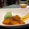 Langostino (ossia gamberone) en suquet, con gnocchi di patata, aria di prezzemolo, crema di zafferano e patata. Sul fondo si vede anche il Capucchino de suquet