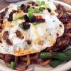 """Jajangmyeon con salsiccia di maiale, chili pan meee uovo fritto. Jajangmyeon è una specialità sudcoreana che, nelle sue formulazioni variabili, prevede sempre dei noodle e della salsa chunjang (pasta salata di soia nera). Li abbiamo assaggiati al Nishi, l'ultimo nato (a gennaio 2016)del marchio Momofuku, il primo apertonel West Village di Manhattan (Nishi vuol dire appunto """"West""""). La curiosità? Oltrealle specialità dalla cucina coreana, il menu ha una vasta sezionedi piatti creativi sumatrice italiana, dalla Lattuga croccante con bagnacoda di noci agli Spaghetti cacio e pepe con uovo fritto sopra"""