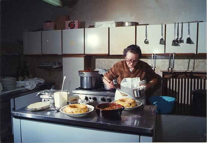 """Mirella Del Nevo al lavoro in cucina. Il gastronomo Toni Sarcina una volta le chiese il motivo dei """"23 tuorli per ogni chilogrammo di farina"""" e lei rispose: «Come vedi, non sono un tipo tranquillo e qualche volta Peppino, con le sue critiche, mi innervosisce; un giorno di molti anni fa stavo facendo la sfoglia e, dopo una discussione su un piatto, ero abbastanza irritata e, dividendo i tuorli dagli albumi, parlando nello stesso tempo, continuavo a rompere le uova mettendole al centro della """"fontana"""" di farina e non mi ero accorta di aver messo 23 tuorli; che fare, buttare tutto? Nemmeno per sogno! E feci l'impasto; era buonissimo, giallo e le tagliatelle fantastiche. Da quel momento, la pasta all'uovo della mia cucina fu fatta da 23 tuorli per chilo di farina»"""
