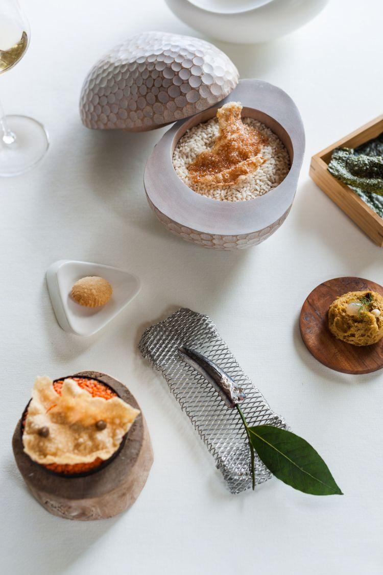 Il primo passaggio del menu degustazione 2021: Chips dipatate e alghe, ditapioca e katsuobushi, dilenticchie e miso di lenticchie. La spugna è di cozze consardella calabra elimone.Il Cracker di baccalà mantecato e la Sardina alla brace conolio di cipollina