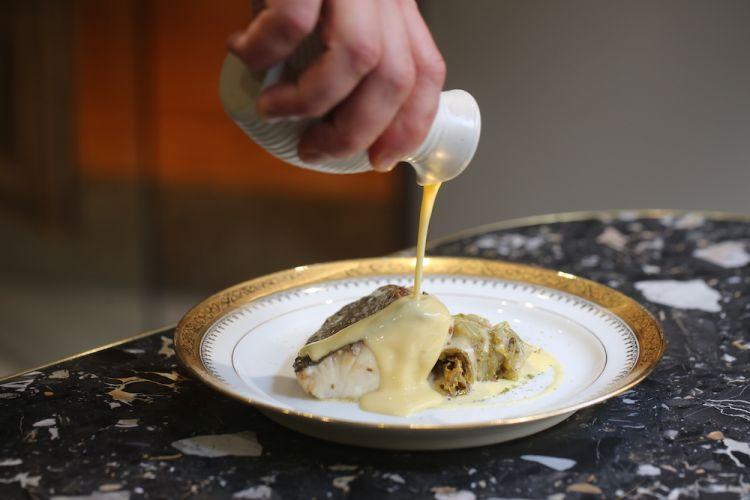 Dentice pescato del Mar Ligure con salsa al Martini Dry e anice, scarola brasata alla liquirizia e burro alla camomilla. Alla base un tocco di polvere di alloro