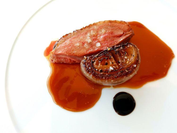 Anatra con cipolla rossa cucinata nel forno di argilla.Come accompagnamento, insalata di cipollotto e peperoncino, tartina di ceci con mousse di anatra e foglie di shiso rosso
