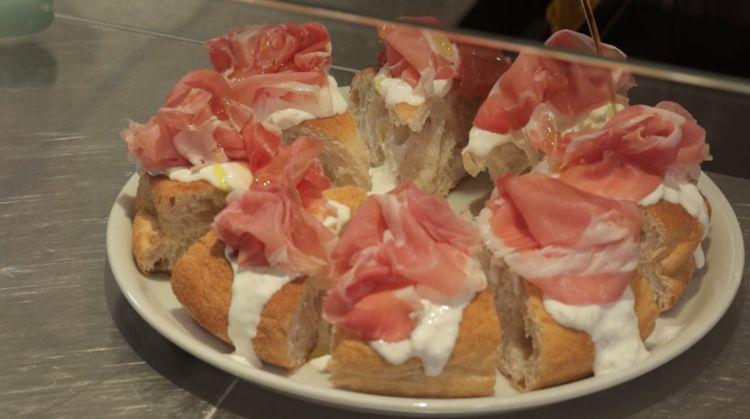 Aria di pane con burrata pugliese e prosciutto crudo di Parma. Bosco ce ne offre un sample nella clip di Identità on the road