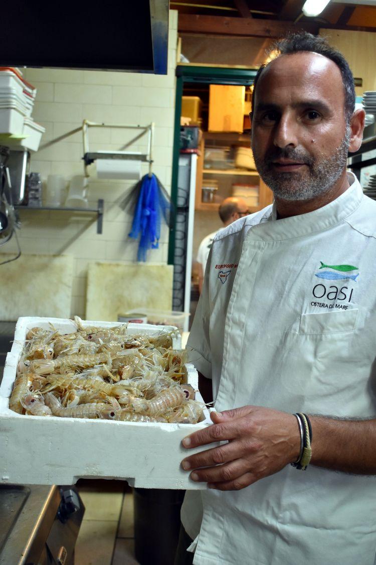 Giovanni Morello con una cesta di canocchie appena consegnate. «L'Oasi è un porto di mare, arriva pesce appena pescato in continuazione»