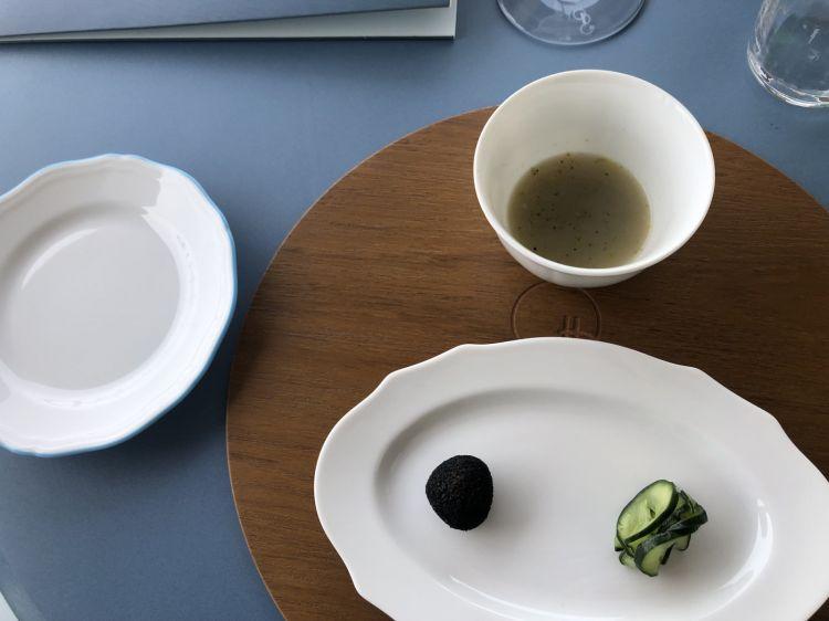 Benvenutia Gabicce Un'entrée tri-composta. In alto a destra, il mare: brodo leggero di cozze alla marinara con alghe e lime. In basso a sinistra,il Montefeltro, un'oliva all'ascolana ripiena di tartufo. In basso a destra,la Campagna di Casa Marcon, l'orto di proprietà a 500 metri dal ristorante: cetriolini lavorati come uno tsukemono (sale, poi conditi con un po' di aceto e olio alla menta).