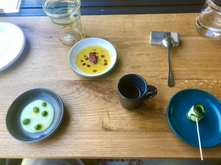 The welcome at LeCementine: left to right, Cream of peas aromatised with basil, Oil and tomato confit,Reduced onion spring broth with thyme, and Courgette carpaccio with mulberries from the garden