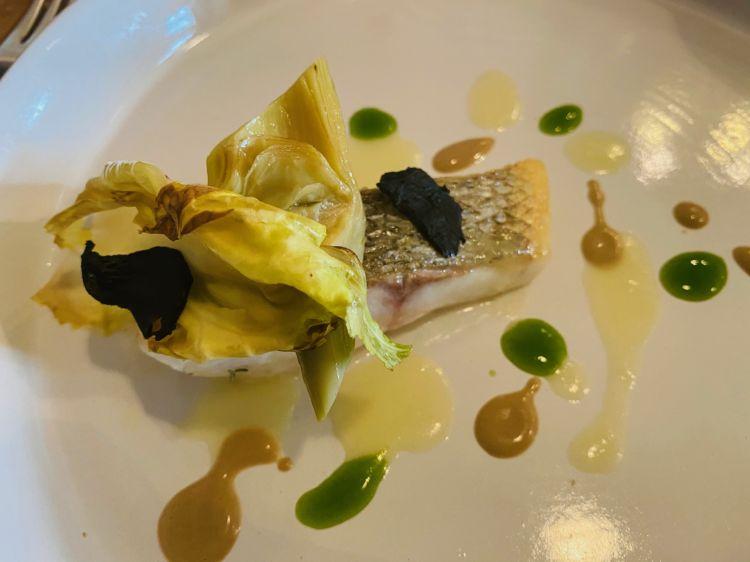 Branzino con carciofi violetti, salsa ai limoni fermentati, tapenade di olive taggiasche e raviola ripiena di gamberi e salsiccia di Bra