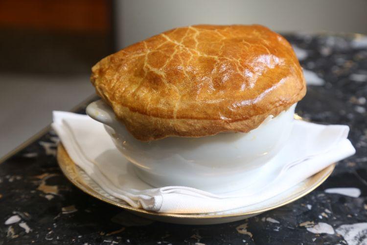 Soupe Aux Truffes VGE, omaggio a Paul Bocuse: sotto la pasta sfoglia, zuppa dell'Eliseo con foie gras tagliato a cubetti, consommè chiaro di pollo, tartufo nero