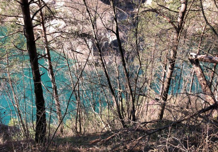 Dietro gli alberi, si intravedono i resti della dogana della Valvestino