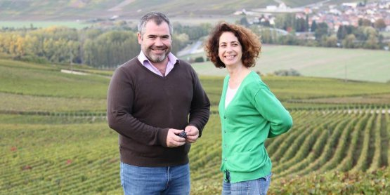 Benoit and Mèlanie Tarlant, with their vineyards behind them