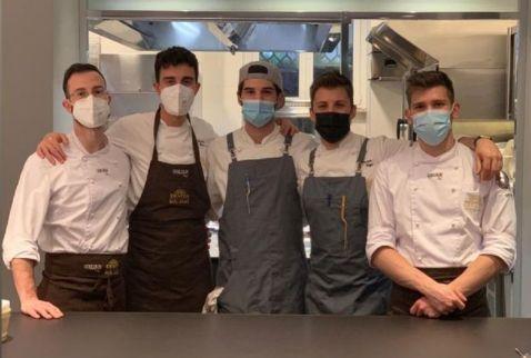 Lorenzo Cogo al pass di Identità Golose Milano con due ragazzi della sua brigata e la squadra di cucina dell'Hub