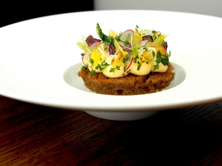 Parmigiano Reggiano 40 mesi, disco di segale, cetrioli e cipolla, del ristorante Phoenix in Germania
