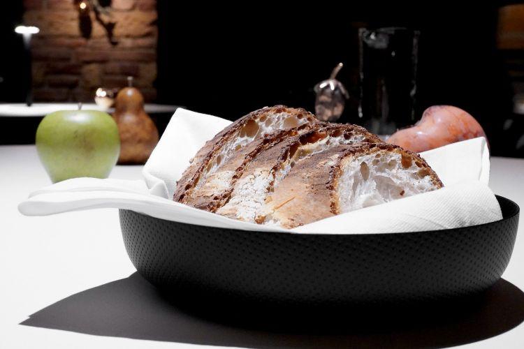 Il pane maison (lievito madre, farina di grano duro). Viene servito insieme a olio evo da varietà Leccio dell'azienda agricola Sisure e burro di capra aromatizzato con cumino