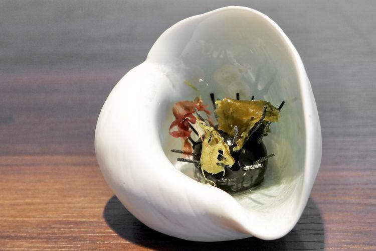 """Riccio: è una mousse di riccio di mare (che viene pastorizzato per renderlo fruibile tutto l'anno) con panna, olio evo, sale, pepe e gel alimentare. Esternamente viene colorata con il nero di seppia. Gli aghi sono grissini al nero, """"sporcati"""" con delle alghe. Il tutto è di eccezionale bontà"""