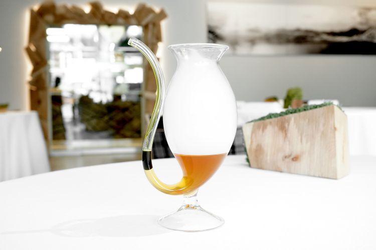 """S'inizia con una deliziosa Acqua di zucca con olio di prezzemolo. È anche divertente: il commensale è chiamato a soffiare dentro la cannuccia di vetro del bicchiere per """"fare le bolle"""": esce il fumo (effetto spettacolare) e olio e acqua si mischiano assieme"""
