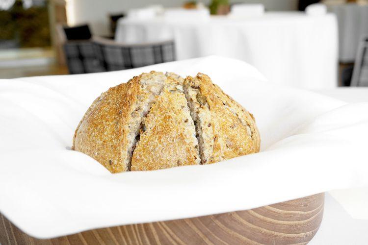 Il pane maison da lievito madre, farina integrale e semi. Viene accompagnato da un burro straordinario, che Griffa ottiene mantecando due burri valdostani diversi, con un po' di sale