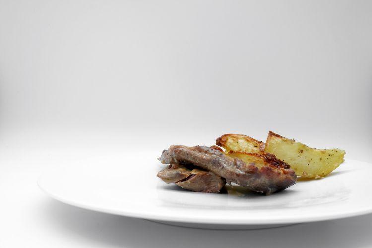 Agnello cotto lentamente con salsa al limone e patate al forno