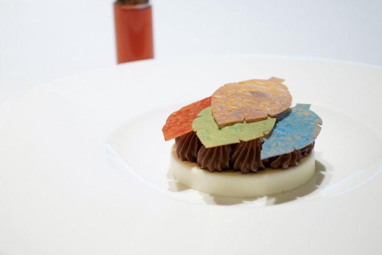 Chiudiamo con un omaggio a Magritte (e all'esperienza dello chef in Belgio): il piatto si chiama Fuoco e si compone di cremoso allo yuzu, ganache all'olivello spinoso, riduzione di birra scura, speculoos, crumble di limone e cannella, foglie di mela croccanti. Un assaggio per niente banale