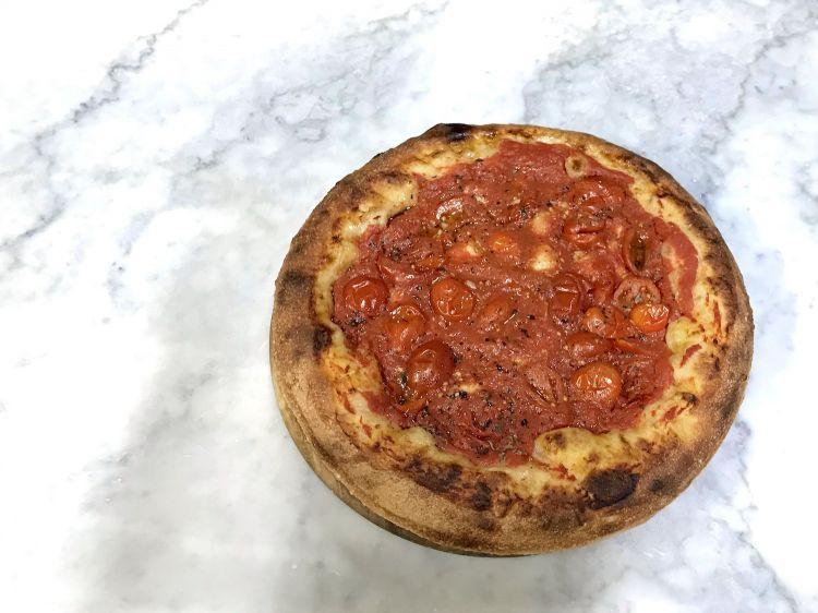 """La """"pizza del giorno dopo"""" di Franco Pepe, impasto doppio in teglia condito semplicemente con pomodoro, cipolla, aromi"""