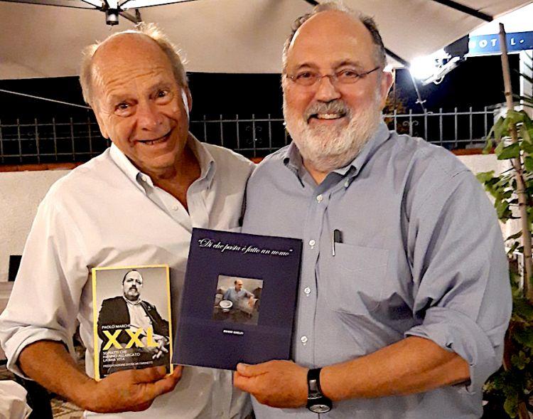Mario Guelfi e Paolo Marchi posano sorridenti ognuno con il libro dell'altro
