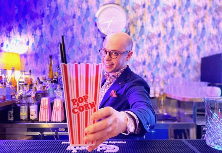 Il bartender Eros Altavela con il cocktail Sex in the cinema, a base di succo di ananas, latte di anacardo, rum, boubon, sciroppo di pop corn e pop corn