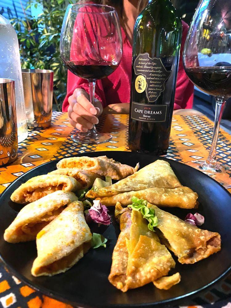 I sambusa sono croccanti triangoli fritti che possono essere ripieni di carne o verdure miste. Sono perfetti per l'aperitivo o l'antipasto con un calice di vino sudafricano
