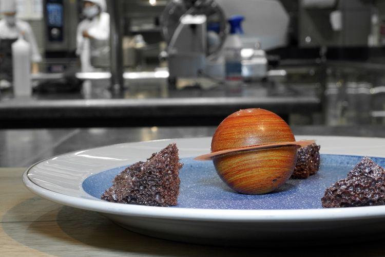 """Universo: sul fondo un burro di cacao, le """"rocce"""" sono di cioccolato fondente soffiato, Saturno è composto come unForesta Nera, con mousse di vaniglia di Tahiti, cuore alla ciliegia e pasta frolla al cioccolato"""