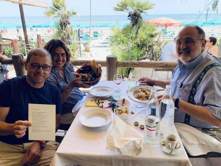 Michele Alesiani regge nella mani il menù del Don Diego, il ristorante sul mare aperto da suo figlio Zaccaria tra aprile e maggio 2021 sulla spiaggia di Grottammare. A tavola con lui Luisa e Paolo Marchi