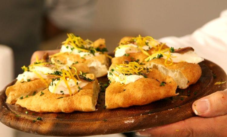 ...e l'Acciugrana, una pizza fritta che oltre alla crema di Grana Padano è preparata con acciughe di Cetara, spezie eagrumi
