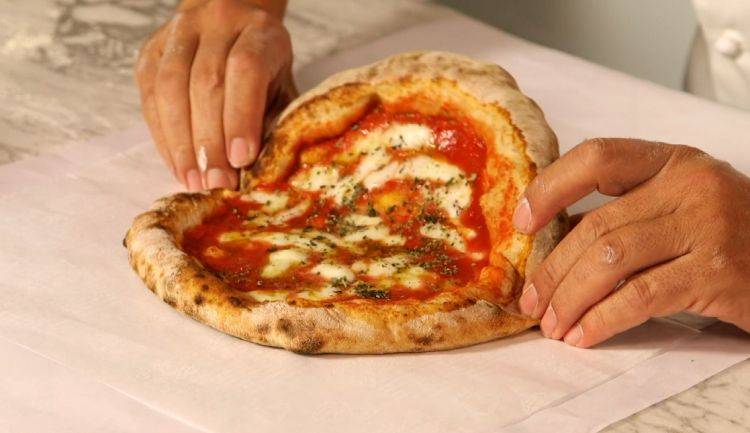 Mediterranea al cartoccio: the pizza is folded and wrapped in greaseproof paper, preserving its aromas differently from what happens with take-away cartons, and making it more sustainable
