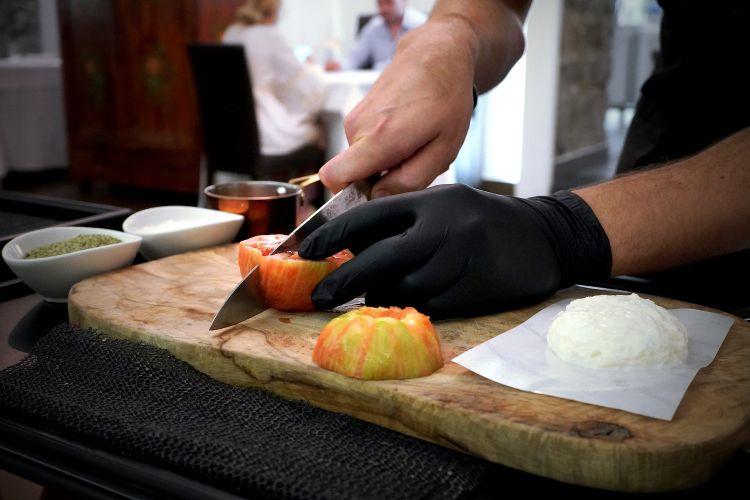 Maicol Izzo al tavolo pela un pomodoro di Sorrento, lo taglia a metà...