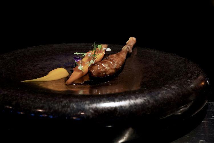 La coscia del piccione con la sua demi-glace, la carota osmotizzata, una salsa di carote e zenzero. A parte, un brodo di piccione speziato