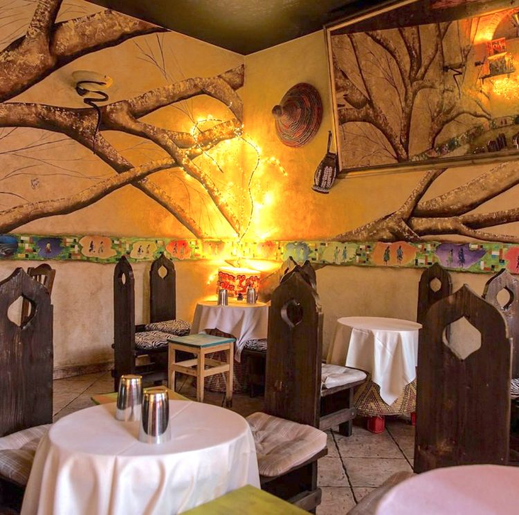 L'interno del ristorante Savana eritreo. Si può mangiare all'esterno, sui tavoli classici, o sui tavolini bassi che si chiamano Mosob, tipici dell'eritrea