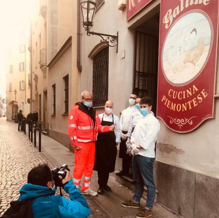 Andrea Chiuni, il responsabile di Croce Verde Marco Crema e alcuni ragazzi del ristorante Tre Galline fotografati da un reporter di France Press