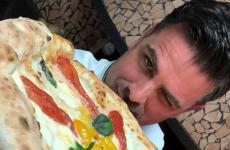 Savino di Noia, cuoco dell'dell'Antica Cantina Forentumdi Lavello (Potenza), regge una pizza con pomodoro San Marzano Dop, pomodorino giallo e bufala