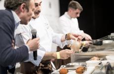 Anthony Genovese prepara il piccione sul palco di Meet in Cucina Abruzzo, sotto gli occhi di Antonio Paolini. Sul tagliere anche i cachi, rimasti tre settimne appesi ad appassire. Genovese sarà anche a Identità Milano 2018, sabato 3 marzo alle ore 12,15