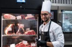 Giovanni Lo Monaco, cuoco figlio di un macellaio, ritratto di fianco a uno dei punti di forza del suo ristorante:la camera di frollatura delle carni