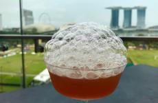 Un drink (l'Old & New Sling del Smoke & Mirrors) con vista su Singapore. La città-stato affascina con i suoi magnifici cocktail bar