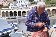 Un anziano pescatore ripara le reti nel porto di Ustica. Tutte le foto sono diGiulia Monteleone, salvo dove diversamente specificato